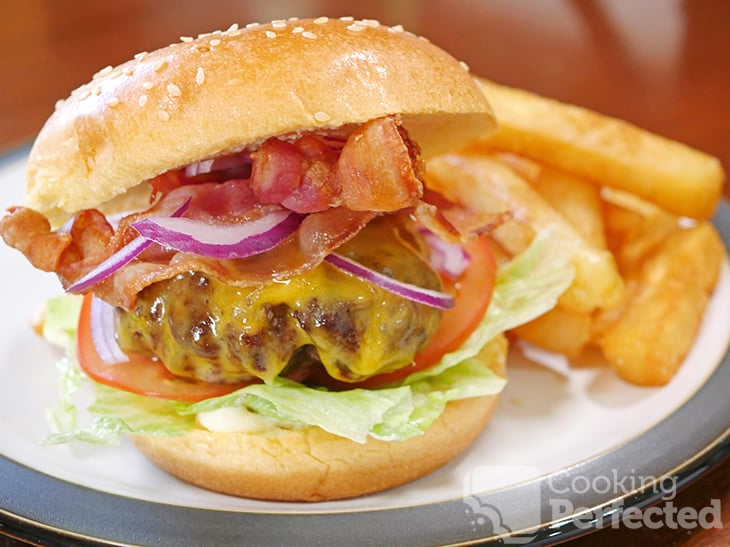 Air fried burger served inside a burger bun with lettuce, tomato, bacon, cheese