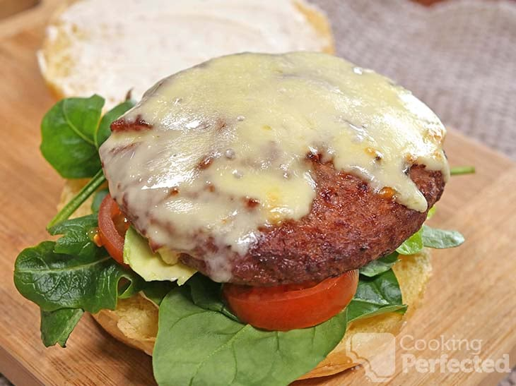 Cooked frozen hamburger on a burger bun with lettuce and tomato.